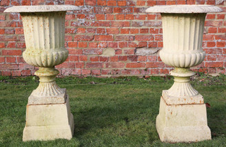 Pair of classical cast iron planters urns on plinths
