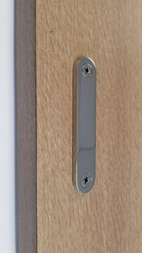 Low-Profile Back-to-Back Sliding  Door Pull  (Polished Stainless Steel Finish) mockup on wood door