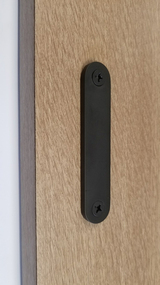 Low-Profile Back-to-Back Sliding  Door Pull (Black Powder Stainless Steel Finish) mockup on wood door