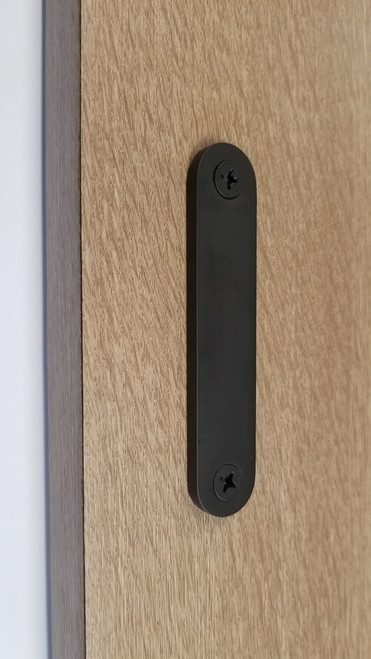 Low-Profile Back-to-Back Sliding  Door Pull (Black Powder Stainless Steel Finish) mockup on wood door