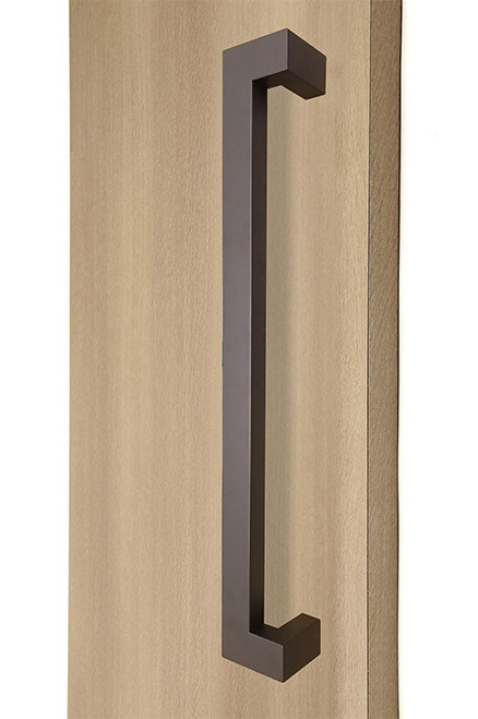 """45º Offset 1.5"""" x 1"""" Rectangular Pull Handle - Back-to-Back, Bronze Finish, 304 Exterior Grade Stainless Steel Alloy mockup on wood door"""