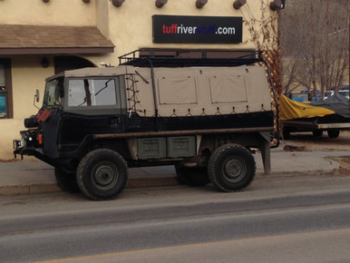 A pinzgauer parked in front of the Tuff River Stuff shop, sporting a custom Tuff River Stuff insulated cover!
