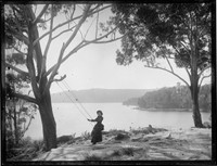 Girl on swing at Folly Point, with view to Warringah Lodge, Cremorne Point & Sydney Harbour in distance behind.