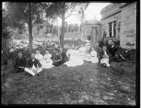 Macpherson family group & workers (16) seated under trees on grass with side façade of Warringah Lodge,  Cremorne.