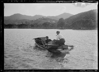 Two moustachioed men crossing lake in row boat laden w. heavy boxes to shore w. distant view to house on hill.