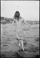 Girl at Clovelly Beach – facing the water with hands on hips in wet cossie.