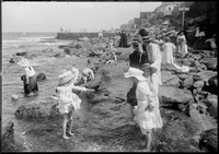 Children paddling in rock pools w. swimming baths behind