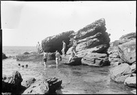 Men swimming in rock pool – several naked and standing, others in water.