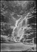 Woman seated on rocks at base of Waterfall.
