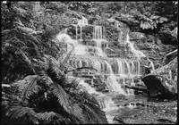Man seated on rock ledge at base of Waterfall.