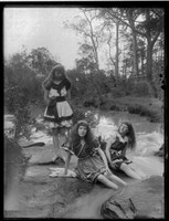 Three Macpherson girls in swim dresses beside creek in bushland setting.