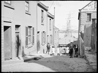 Children standing in Unwin Street, Millers Point, with view to harbour behind and photographer's shadow.