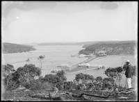 Macpherson male on hillside overlooking Spit w. view to 'A. McKaye's Refreshment Rooms', 'Lyons Boatshed', Sydney Harbour & ferry in background.