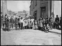 Children standing across Hart St, Millers Pt, boy at centre holding broken timber paling.