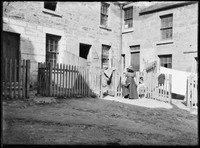 Woman and two children standing near gate and paling fences behind slum houses at The Rocks.