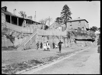 Looking south along Trinity Ave, Millers Point, w. row of houses on rock ledge and group of children standing below.