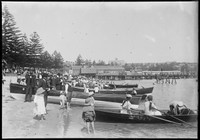 View across Manly Cove to Ferry Wharf with crowds on sand and people in boats and St Patrick's Seminary on hill behind.