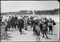 Children on beach with clown at Coogee, with Coogee Palace Aquarium (1887-1986) in background.