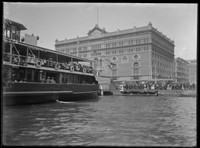 Ferry docking at Circular Quay in front of Goldsborough Mort & Co. building w. crowds.