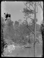 View across cove to 'Warringah Lodge', North Cremorne, with man seated on shoreline and boat in foreground.