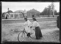 One girl helping a second to ride bicycle next to dirt road w. row of timber buildings behind.