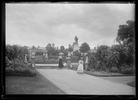 Women strolling down stone stairs leading into Royal Botanic Gardens w. view to Governor Phillip fountain and Macquarie St terraces behind.