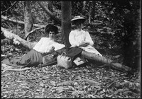 Two Macpherson women seated in bush setting.