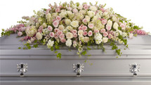 Adored White & Pink Rose Casket Cover Spray from Sympathy Flower Shop. It includes pink hydrangeas, larkspur and roses mingled with white roses, stock and waxflower. Then ivy, fern and fragrant eucalyptus act as green accents in this spray that rests atop the casket.  SKU SYM811