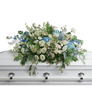 White Roses and Blue Flowers Casket Cover from Sympathy Flower Shop. A stunning spray of flowers includes blue hydrangeas, white roses, mini white spray roses, white alstroemeria, white stock, blue delphinium, white lisianthus, white larkspur, white waxflower, dusty miller, and various greenery including eucalyptus and sword fern. SYM805