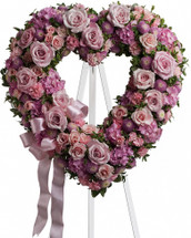 "Garden of Roses Pink Shaped Open Heart of Funeral Flowers from Sympathy Flower Shop. Lovely flowers in this heart shaped spray include light pink roses, pink hydrangeas and miniature pixie carnations mixed with lavender buttons. Approximately 19"" W x 19"" H SKU SYM101"