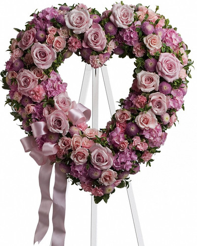"""Garden of Roses Pink Shaped Open Heart of Funeral Flowers from Sympathy Flower Shop. Lovely flowers in this heart shaped spray include light pink roses, pink hydrangeas and miniature pixie carnations mixed with lavender buttons. Approximately 19"""" W x 19"""" H SKU SYM101"""