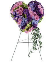 "Graceful Purple and Lavender Heart Tribute Flowers from Sympathy Flower Shop. This heart-shaped sympathy tribute is covered with lavender roses, blue iris and blue hydrangeas and purple chrysanthemums and arrives on a wire funeral easel. Approximately 20"" W x 24"" H SKU SYM107"