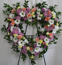 "Loving Lavender & Pink Heart Tribute of Funeral Flowers from Sympathy Flower Shop. This heart shaped funeral spray is created with lavender mums, white daisies, yellow mini pixie carnations, pink mini pixie carnations and light pink spray roses, delivered on a metal funeral easel. Approximately 22"" W x 22"" H  SKU SYM110"