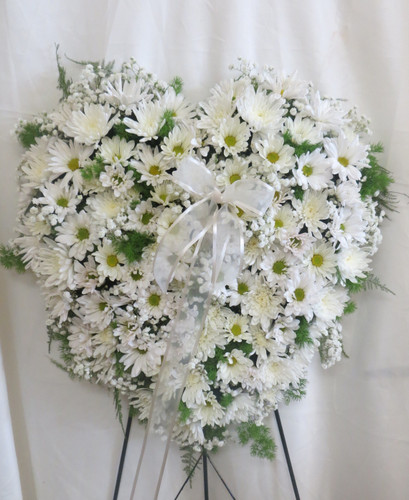 """Purest Soul All White Heart Shaped Funeral Wreath from Sympathy Flower Shop. Our standing spray heart will arrive on a metal funeral easel and includes white daisies, white mums, and white baby's breath throughout the entire heart. Solid white heart is approximately 20"""" W x 22"""" H SKU SYM112"""