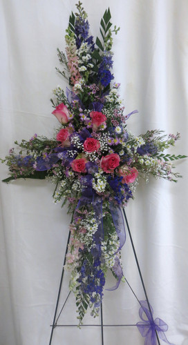"""Grace & Lace Pink, Lavender, and Purple Funeral Cross of Flowers from Sympathy Flower Shop. This heart warming cross of flowers includes hot pink roses, pink and purple larkspur, and other various filler flowers and arrives on a wire funeral easel stand. Approximately 36"""" W x 52"""" H   SKU SYM309"""