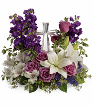 "Purple and Lavender Flowers with Crystal Cross Keepsake from Sympathy Flower Shop. This sympathy bouquet includes lavender roses, white oriental lilies, white alstroemeria, purple stock and purple seafoam statice are arranged with fresh pitta, seeded eucalyptus and lemon leaf. Delivered with the small Crystal Cross keepsake, cross is approximately 7""H x 4""W x 1.5""D. Sympathy flowers are approximately 16"" W x 14"" H SKU SYM471"