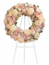 "Eternal Peace White and Pink Funeral Wreath Spray from Sympathy Flower Shop. Gorgeous pink hydrangeas, crème roses, light pink spray roses, white chrysanthemums, waxflower and more are adorned by pink ribbons in this eternal circle of peace. Approximately 22"" W x 22"" H (Size does not include easel) SKU SYM206"