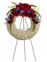 "Glory Reflected Red White and Blue Funeral Wreath from Sympathy Flower Shop. A beautiful array of flowers such as blue hydrangea, red roses and spray roses, delicate blue delphinium, red gladioli, white cushions and more create a circle of serene beauty.  Approximately 24 "" W x 24"" H (Size does not include easel) SKU SYM207"