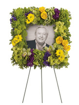 "Richly Remembered Square Photo Tribute Funeral Spray from Sympathy Flower Shop. Stunning flowers such as hydrangea, dazzling green cymbidium orchids, roses, gladioli, bells of Ireland and more make this an incredible display of respect. Approximately 22"" W x 22"" H SKU SYM208"