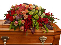 Farewell Orange, Red, and Green Casket Cover from Sympathy Flower Shop. The beautiful casket arrangement includes green miniature hydrangeas, orange roses, dark orange asiatic lilies, red gerberas, red gladioli, green carnations and bells of Ireland, then is accented with assorted greenery.  SKU SYM814
