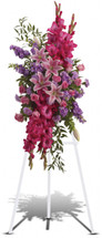 My Touching Tribute Standing Spray from Sympathy Flower Shop. These gorgeous flowers such as pink roses, stargazer lilies and gladioli blend with the purple stock, lavender carnations and fragrant greens. Delivered on a wire funeral stand. Downtown Houston funeral flower delivery. SKU SYM611