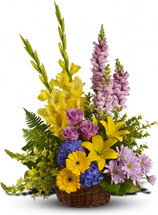 Love's Lemon Tapestry by Sympathy Flower Shop. This funeral bouquet includes yellow gladiolas, yellow lilies, yellow gerberas, lavender cushions, and blue hydrangeas in a wicker basket. Your funeral florist Houston. SKU  SYM404