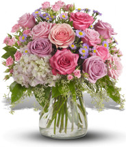 Shining Light Sympathy Bouquet by Sympathy Flower Shop. Lavender and pink flowers such as roses, hydrangea, monte cassino asters, eucalyptus and salal are arranged in a clear glass hurricane vase. SKU SYM427