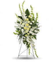 Purely Magnificent Standing Spray by Sympathy Flower Shop.  Our gorgeous array of white roses, white carnations, white gladioli, white stock, white cushion spray chrysanthemums and bells of Ireland is accented with green ti leaves, spiral eucalyptus and lemon leaf, delivered on a funeral easel stand. Free League City funeral home delivery. SKU SYM608
