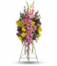 Rainbow Radiance Standing Spray by Sympathy Flower Shop.  Our beautiful standing spray of sympathy flowers includes pink stargazer lilies, yellow gerbera daisies, yellow alstroemeria, pink gladioli, purple carnations and purple larkspur accented with oregonia and lemon leaf. SKU SYM609