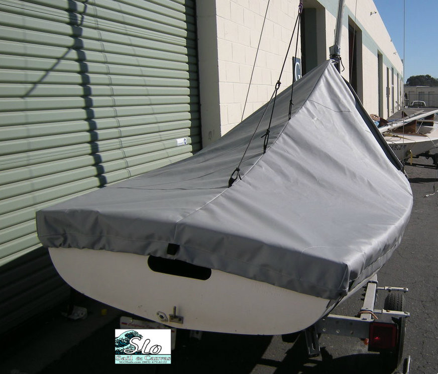 """Flying Junior sailboat Mast Up Peaked Mooring Cover by SLO Sail and Canvas. 1/4"""" shockcord is built into cover to secure your cover tightly around the boat's rubrail. Web Loops allow you to """"tent"""" your cover up to prevent pooling of water. Reinforcements positioned over blocks and cleats prevent chafing."""