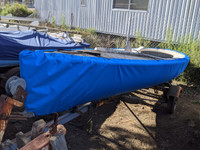 """Finn Sailboat Hull Cover made in America by skilled artisans at SLO Sail and Canvas. 1/4"""" shockcord is built into cover to secure your cover tightly around the boat's rubrail."""