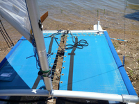 """3pc Textilene 90 premium mesh trampoline to fit a Hobie 3.5 catamaran made in the USA by SLO Sail and Canvas. Hand pounded #4 brass spur grommets. Adjustable hiking straps made of 3"""" Polypropylene webbing. 12"""" X 12"""" halyard pocket, included."""