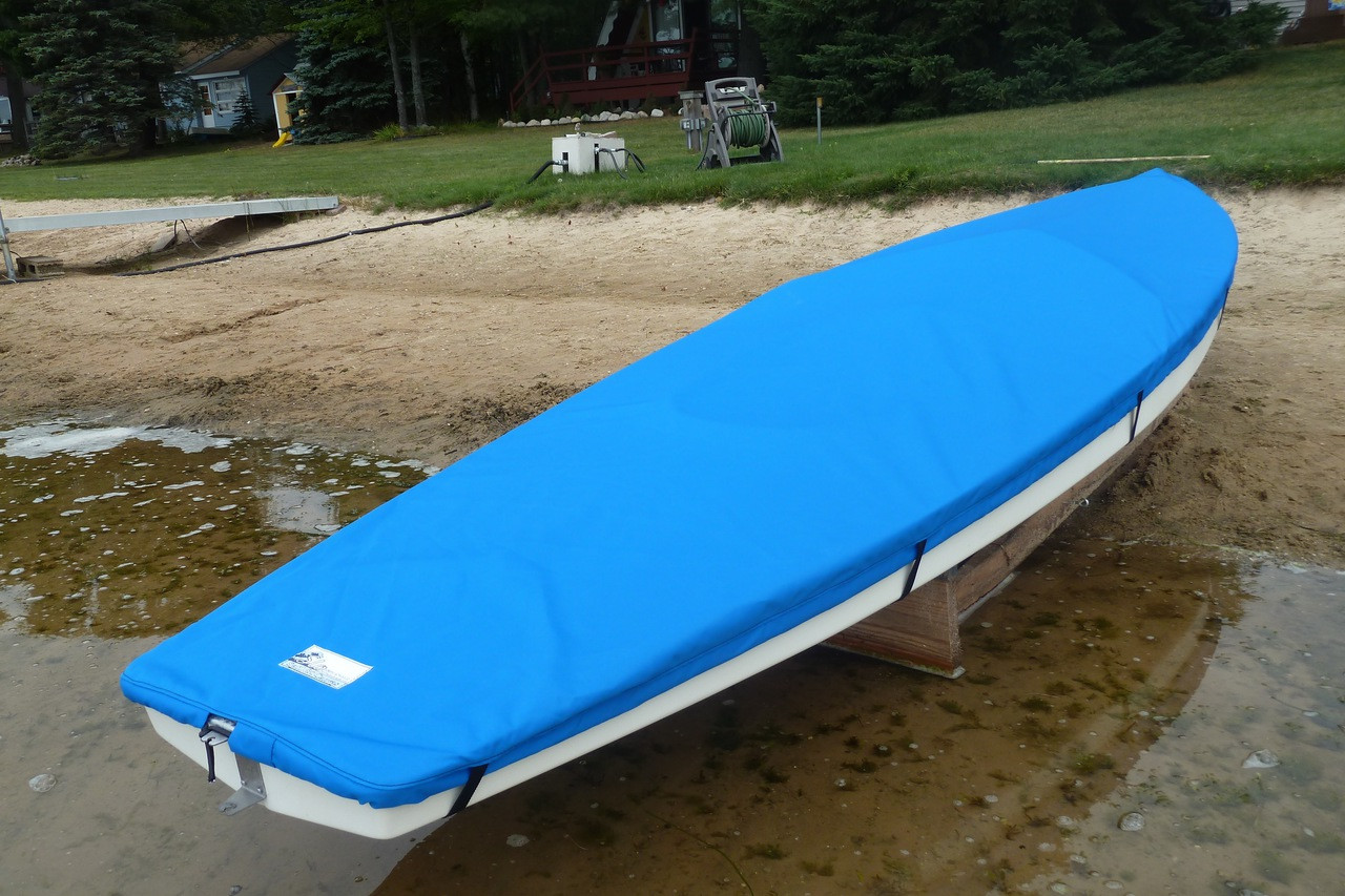 """Sunfish Deck Cover by SLO Sail and Canvas shown in Polyester Royal Blue. Available in 3 fabrics and many color choices. 1/4"""" shockcord is built into cover to secure your cover tightly around the boat's rubrail. Built in rudder gudgeon cutout. Cover your boat with or without rudder attached."""