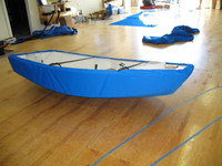 """Sailboat Hull Cover made in America by skilled artisans at SLO Sail and Canvas. 1/4"""" shockcord is built into cover to secure your cover tightly around the boat's rubrail. Polypropylene straps with plastic Fastex buckles included."""